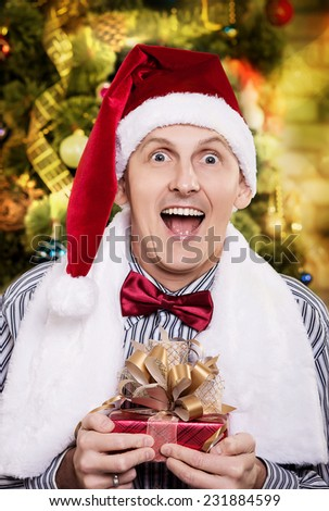 Portrait of a young man in Santa cap. Santa Claus with gifts in his hands - stock photo