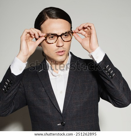 Portrait of a young man in studio on a white background in a suit and glasses - stock photo