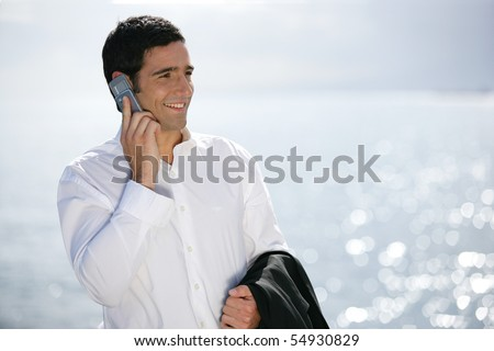 Portrait of a young man in suit phoning - stock photo