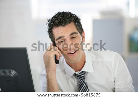 Portrait of a young man in suit phoning in front of a desktop computer