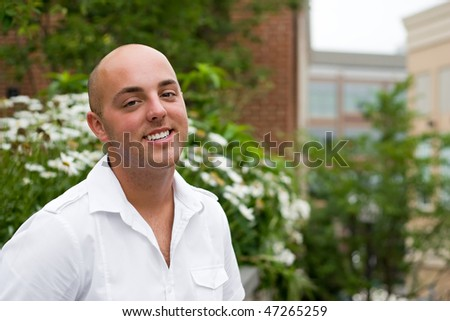 Portrait of a young man in the city by some daisies with copyspace. - stock photo
