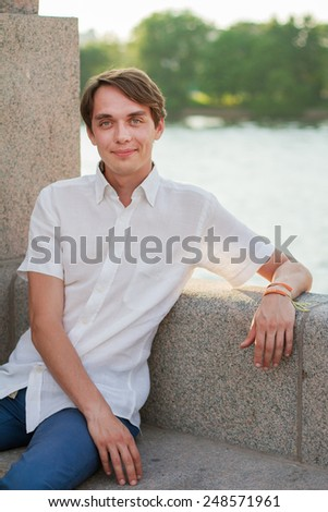 portrait of a young man in the park on a background of lake