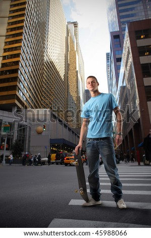 Portrait of a young man in trendy clothes holding a skateboard in the middle of a city street - stock photo