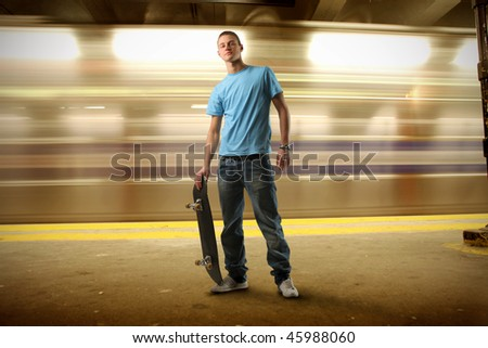 Portrait of a young man in trendy clothes holding a skateboard on an underground platform - stock photo