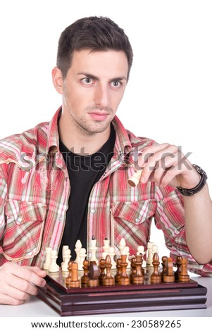 Portrait of a young man is playing a chess on a white background. - stock photo