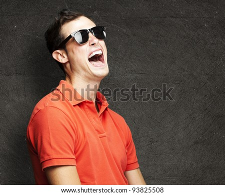 portrait of a young man laughing against a grunge wall - stock photo