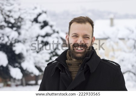 Portrait of a young man Laughing and feeling happy in the snowy winter scenery  - stock photo