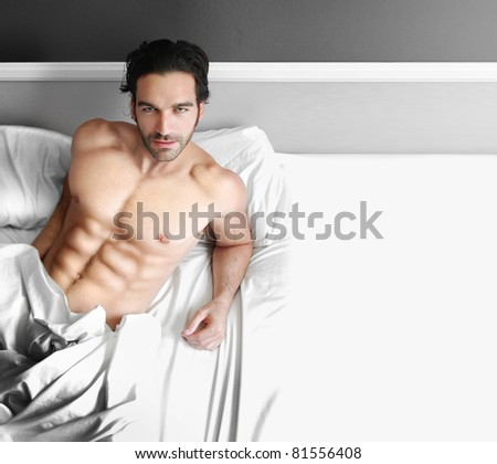 Portrait of a young man laying in bed with copy space - stock photo