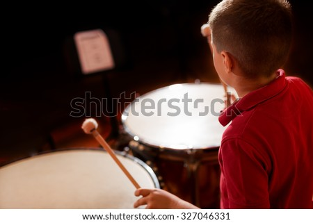 portrait of a young man learning to play the drum - stock photo