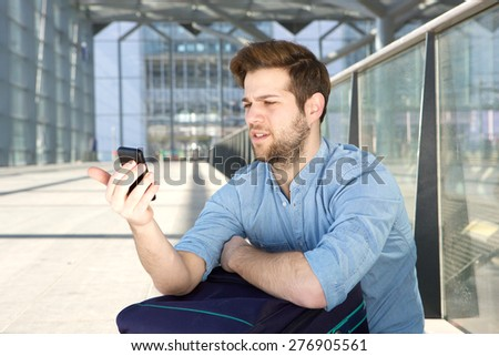Portrait of a young man looking at mobile phone with confused expression on face - stock photo