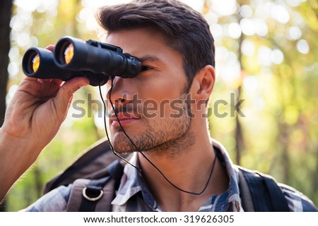 Portrait of a young man looking through binocular in the forest - stock photo