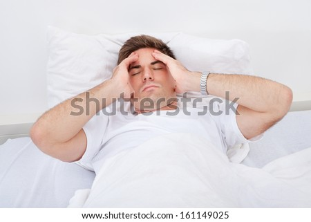 Portrait Of A Young Man Lying On Bed Suffering From Headache - stock photo