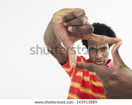 Portrait of a young man making frame with fingers against white background - stock photo