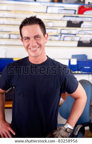 Portrait of a young man mechanic smiling, looking at the camera - stock photo