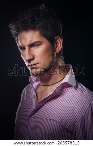 Portrait of a young man on a black background in the studio. A man looks piercing eyes. Man thinks. - stock photo