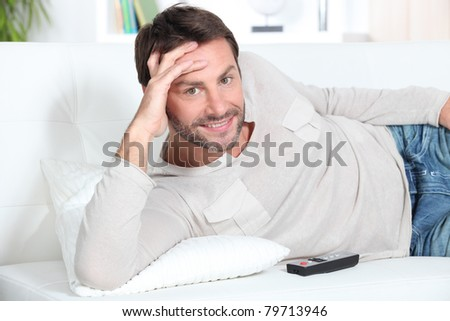 portrait of a young man on couch - stock photo