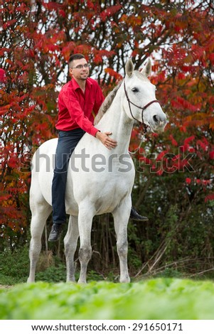 Portrait of a young man on his horse - stock photo