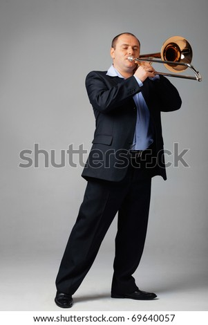 Portrait of a young man playing his trombone. - stock photo