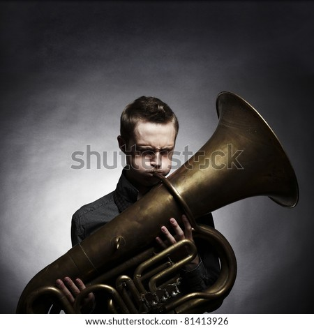 Portrait of a young man playing on the golden tuba - stock photo