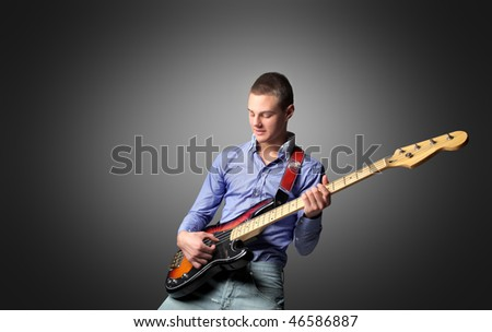 Portrait of a young man playing the bass guitar - stock photo