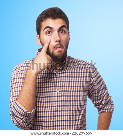 portrait of a young man pointing his eye - stock photo