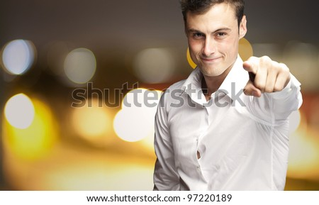 portrait of a young man pointing with his finger at a city by night background
