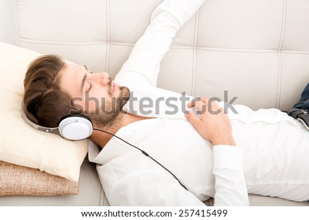 Portrait of a young man relaxing and listening to music on the couch.  - stock photo