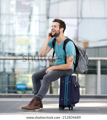 Portrait of a young man relaxing at airport and talking on mobile phone - stock photo
