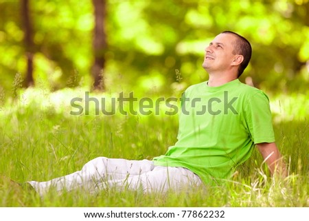 Portrait of a young man relaxing in the forest - stock photo