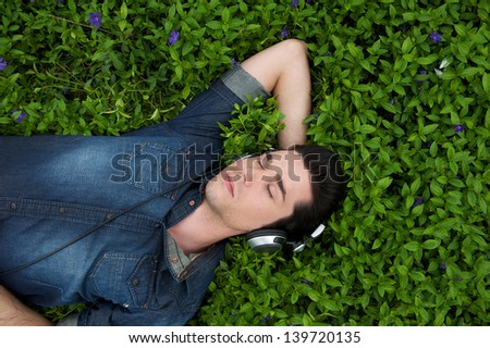 Portrait of a young man resting in the grass with eyes closed listening to music on headphones - stock photo