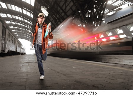 Portrait of a young man running in a train station - stock photo