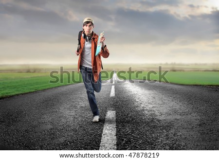 Portrait of a young man running on a countryside street - stock photo