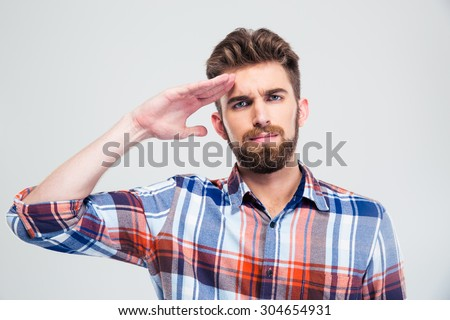 Portrait of a young man saluting isolated on a white background. Looking at camera - stock photo