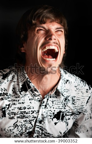 Portrait of a young man screaming out loud against black background - stock photo