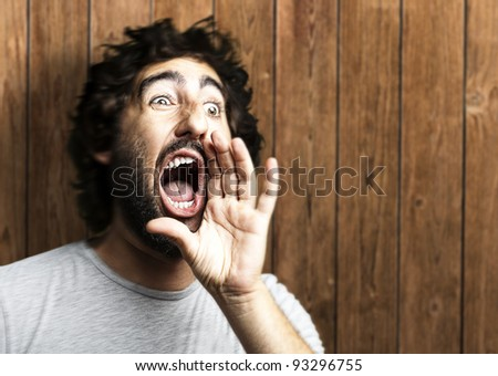 portrait of a young man shouting against a wooden wall - stock photo