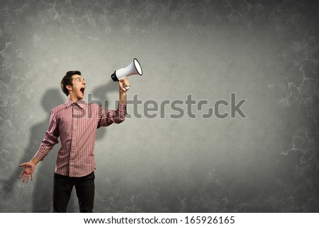 Portrait of a young man shouting using megaphone, behind the concrete wall - stock photo