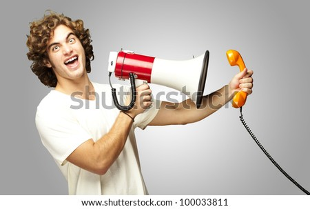 portrait of a young man shouting with a megaphone and talking on a vintage telephone over a grey background - stock photo