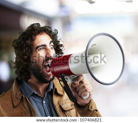 portrait of a young man shouting with a megaphone at a crowded place - stock photo