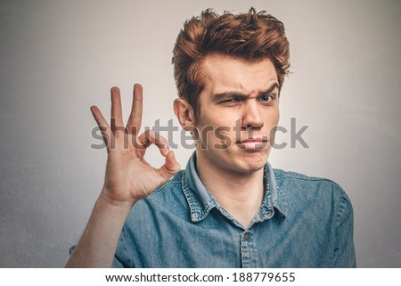 Portrait of a young man showing ok sign - stock photo