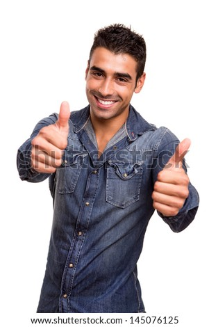 Portrait of a young man showing thumbs up - stock photo