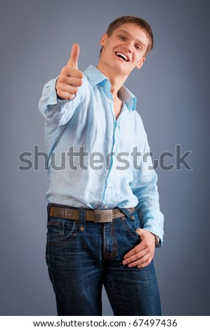 Portrait of a young man showing thumbs up sign - stock photo