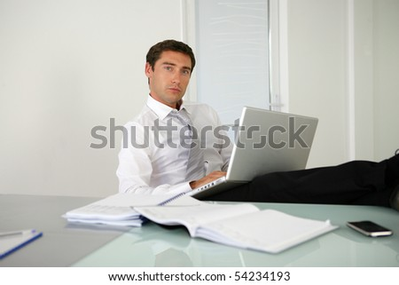 Portrait of a young man sitting at a desk with a laptop computer
