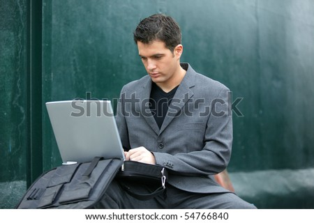 Portrait of a young man sitting in front of a laptop computer - stock photo