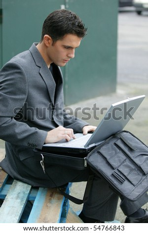 Portrait of a young man sitting in front of a laptop computer