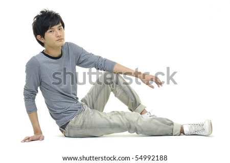 Portrait of a young man sitting on the floor. - stock photo