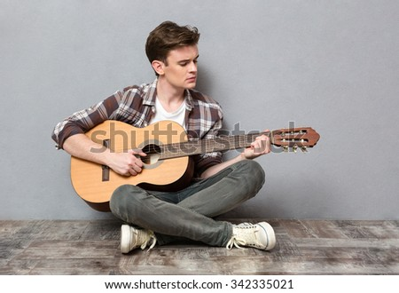 Portrait of a young man sitting on the floor and playing on guitar on gray background - stock photo