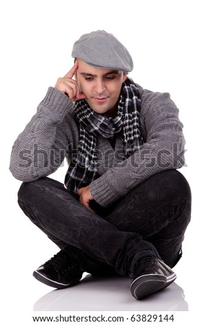 Portrait of a young man sitting on the floor, thinking and looking down, in autumn/winter clothes, isolated on white, Studio shot - stock photo