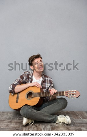 Portrait of a young man sitting on the floor with guitar and looking up at copyspace - stock photo