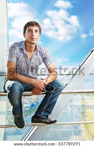 Portrait of a young man sitting on the railing, looking up in thought - stock photo