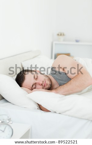 Portrait of a young man sleeping in his bedroom - stock photo
